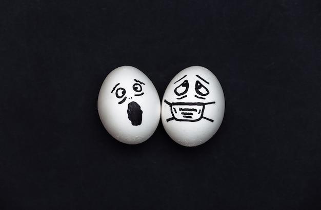 O rosto de ovo em uma máscara médica e com medo em fundo preto. pandemia do covid19. vista do topo
