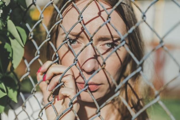 O rosto de uma jovem garota atrás de uma cerca de metal