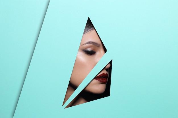 O rosto de uma jovem mulher bonita com uma maquiagem brilhante e lábios vermelhos parece através de um buraco de triângulo em papel verde.