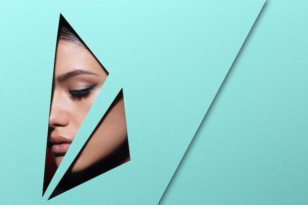 O rosto de uma jovem mulher bonita com uma maquiagem brilhante parece através de um buraco de triângulo em papel verde.