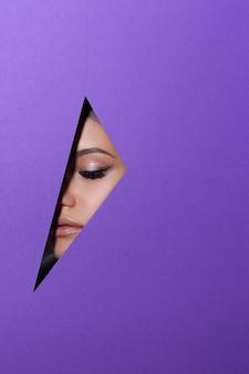O rosto de uma jovem mulher bonita com uma maquiagem brilhante parece através de um buraco no papel violeta.