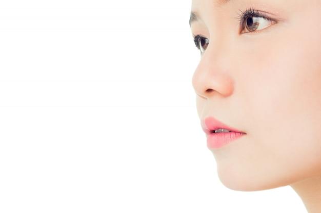 O rosto de uma mulher com boa saúde da pele e lábios cor de rosa