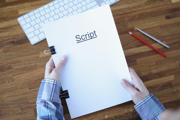 O roteirista mantém uma pasta de documentos rotulados como script. desenvolvimento de tramas para filmes e
