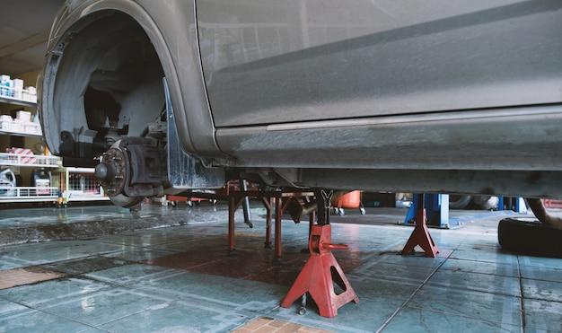 O rotor do disco do freio do carro removeu o pneu para trocar o disco antigo, faça a manutenção do veículo da peça nova na garagem.