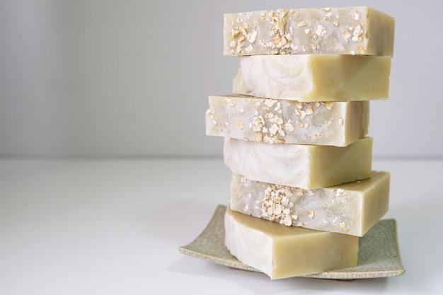 O sabão natural da farinha de aveia é colocado em um fundo branco.