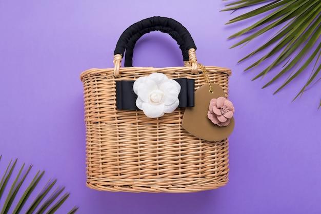 O saco da mulher de vime moda na superfície violeta ou roxa, close-up, conceito de viagens e férias, vista superior, conceito de verão