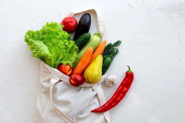 O saco de matéria têxtil encheu-se com vegetais e frutas, vista superior no fundo branco.
