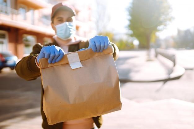 O saco de papel com comida e café nas mãos do correio na cidade de quarentena. serviço de entrega em quarentena, surto de doença, condições pandêmicas de coronavírus covid-19.