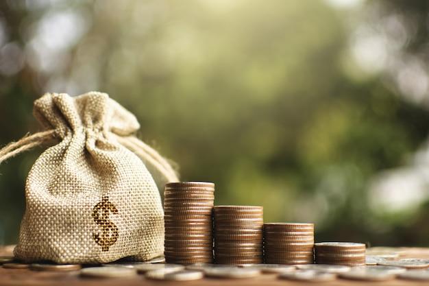 O saco do dinheiro com moedas na prancha de madeira e no fundo do bokeh da árvore.