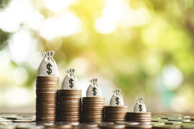 O saco do dinheiro com moedas no fundo de madeira da prancha e do bokeh da árvore, começa planear a economia para o negócio e o estilo de vida.