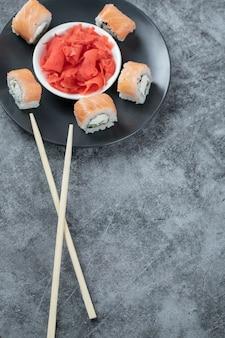 O salmão rola em um prato preto com gengibre vermelho marinado.