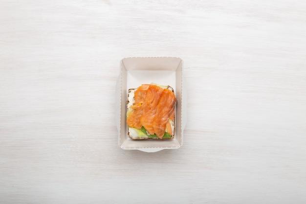 O sanduíche de vista de cima com queijo macio e peixe vermelho encontra-se na lancheira ao lado das verduras e tomates em uma parede branca com espaço de cópia. conceito de um lanche saudável.