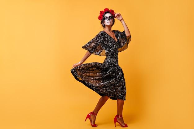 O sangue quente de uma mulher latina com rosas no cabelo escuro a faz mudar para melodias tradicionais para o halloween. modelo posando com maquiagem em forma de caveira em parede laranja