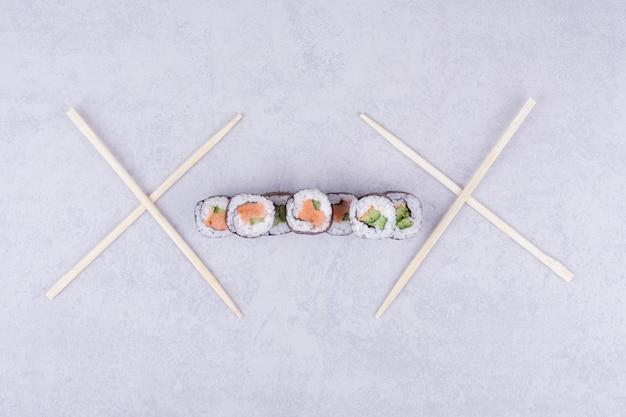 O saquê maki rola com salmão e abacate no cinza.