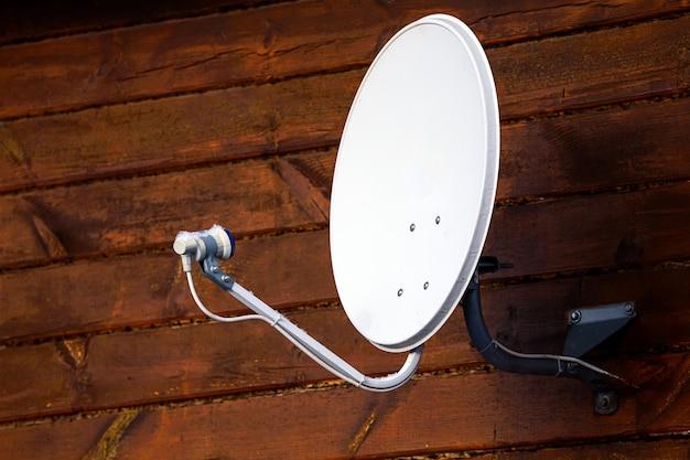 O satélite está preso à parede da casa de madeira