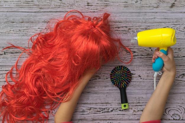 O secador de cabelo na mão da criança aponta para uma peruca laranja brilhante. acessórios para criar penteados e cuidados com os cabelos.