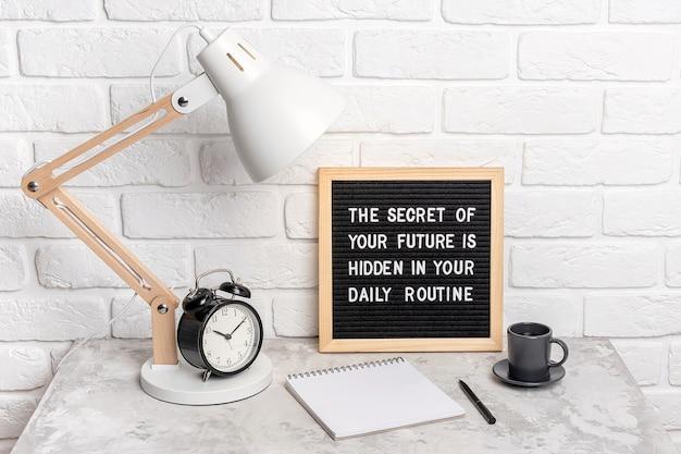 O segredo do seu futuro está escondido na sua rotina diária. citação motivacional no quadro de correspondência, despertador, lâmpada no local de trabalho. citação inspiradora do conceito do dia. vista frontal.