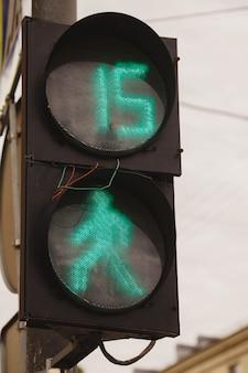 O semáforo verde e os pedestres estão acesos no semáforo com fios para fora. faixa de pedestres na cidade. o número 15 no semáforo deixa claro que os pedestres atravessam a rua por quinze segundos