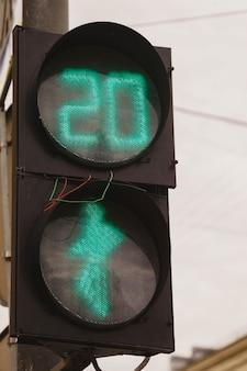 O semáforo verde e os pedestres estão acesos no semáforo com fios para fora. faixa de pedestres na cidade. o número 20 no semáforo deixa claro que os pedestres atravessam a rua por vinte segundos