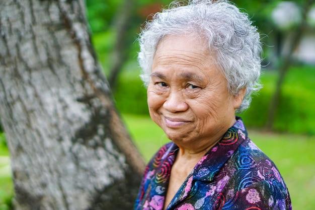 O sênior asiático ou a mulher idosa da senhora idosa sorriem face brilhante com saúde forte.