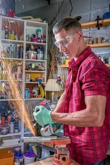 O serralheiro corta o metal com uma máquina de retificar, a serra mecânica corta.