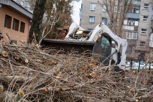 O serviço de emergência urbana remove uma árvore caída em uma estrada com um traktor de equipamento especial.