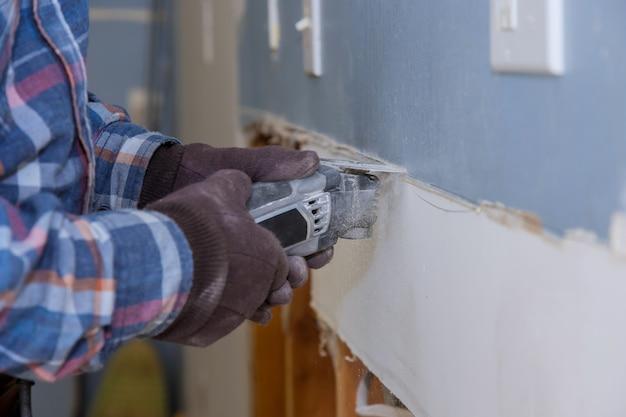 O serviço de renovação de casa trabalha no trabalho de corte de gesso cartonado com a construção de uma serra ferramentas elétricas de substituição de drywall danificado