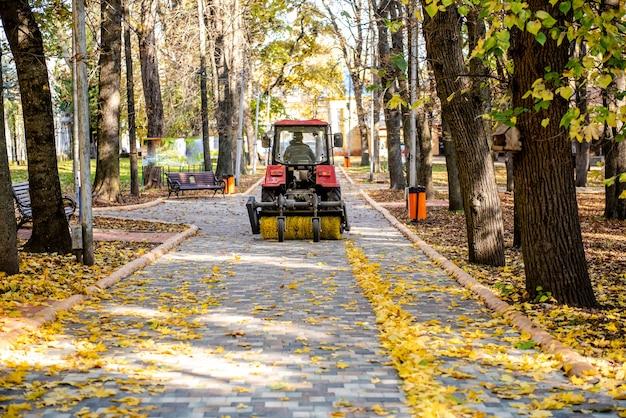 O serviço municipal realiza trabalhos de outono no parque retroescavadeira coleta um monte de folhas
