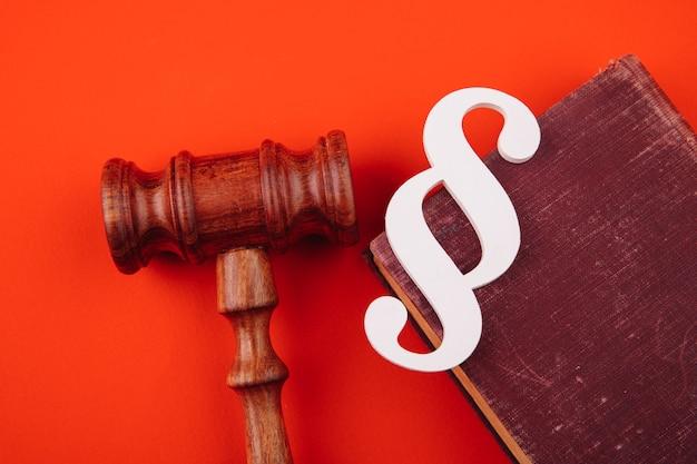 O símbolo de parágrafo branco está em um livro de leis e o martelo sobre fundo vermelho.