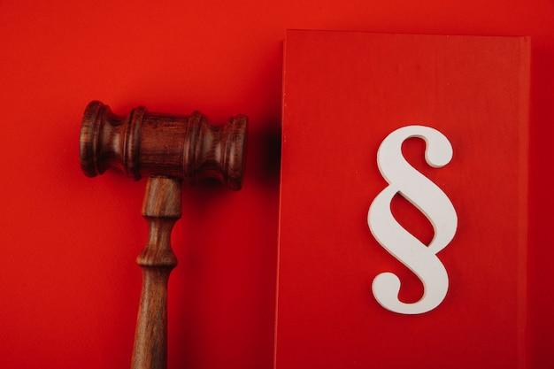 O símbolo do parágrafo está em um livro e o martelo sobre fundo vermelho.