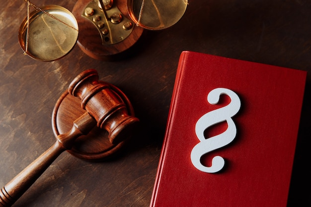 O símbolo do parágrafo está no livro de leis vermelho e o martelo no conceito de lei e justiça do tribunal