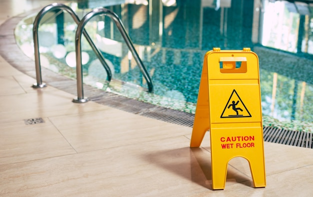 O sinal amarelo da placa de piso molhado está perto da piscina.