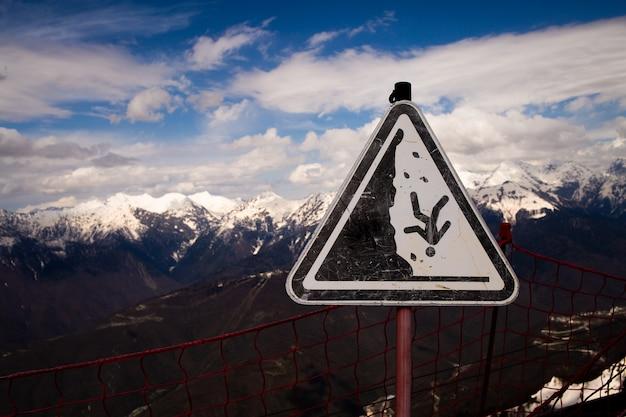 O sinal de cuidado pode cair do penhasco. aviso. o perigo de cair o sinal de alerta no lado de uma montanha íngreme. foto de alta qualidade