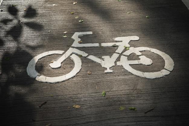 O sinal de maneira de bicicleta no chão de concreto