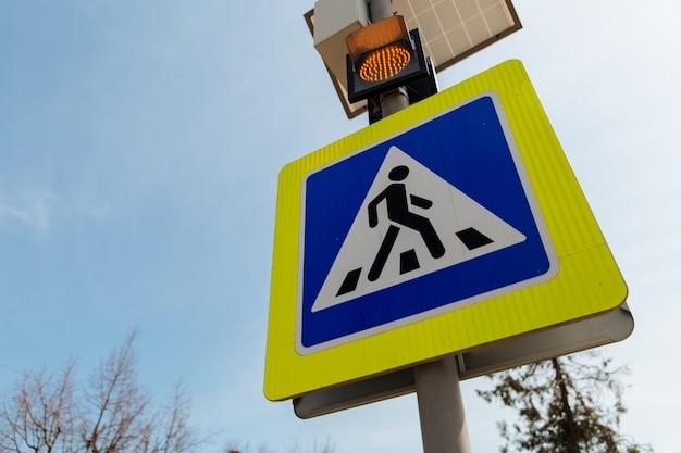 O sinal de passagem de pedestres alimentado por painéis solares instalados acima dos sinais e regras de trânsito