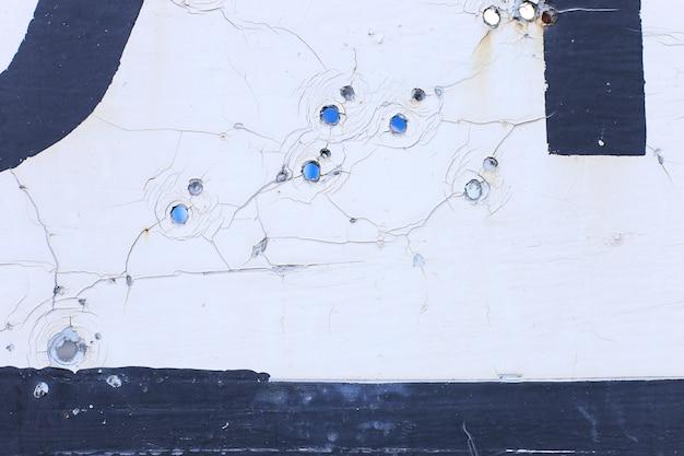 O sinal de trânsito da aldeia, no lugar de hostilidades. buracos de bala em metal.