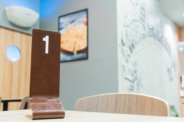 O sinal número 1 está localizado na mesa de jantar dentro do restaurante.