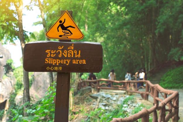 O sinal que mostra um meio escorregadiço da área, o tailandês e o chinês do alfabeto beware escorregadiço.