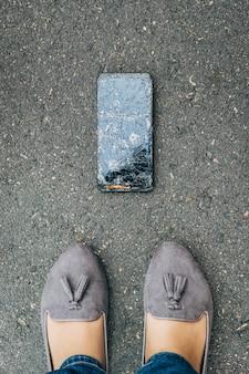 O smartphone caiu no chão com o dono olhando para o telefone com a tela quebrada.