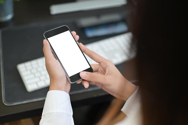 O smartphone do modelo na fêmea entrega a exposição vazia na tabela do escritório com fundo do borrão.