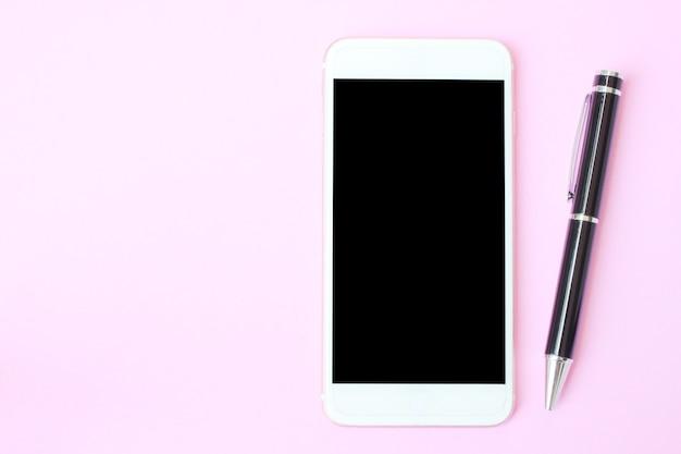 O smartphone e a pena da vista superior no assoalho cor-de-rosa e têm o espaço da cópia.