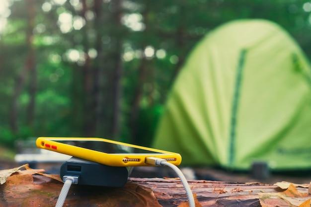O smartphone é carregado com um carregador portátil. power bank carrega o telefone ao ar livre com uma mochila contra o pano de fundo de uma barraca.