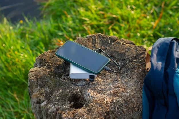 O smartphone é carregado com um carregador portátil. power bank carrega o telefone ao ar livre com uma mochila para turismo na natureza.
