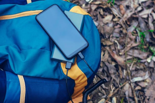 O smartphone é carregado com um carregador portátil.