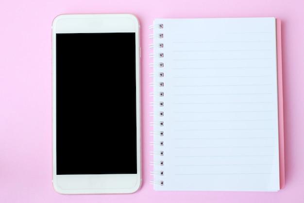 O smartphone e o caderno da vista superior no assoalho cor-de-rosa e têm o espaço da cópia.