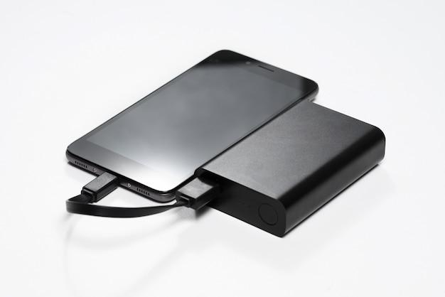 O smartphone está carregando do banco de energia da bateria preto