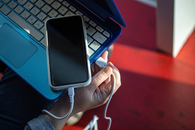 O smartphone está conectado ao laptop por meio de um cabo usb
