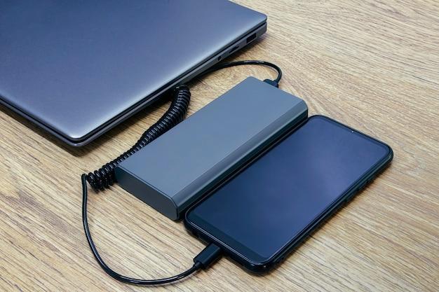 O smartphone está sendo carregado em um banco de energia. carregador portátil com laptop em uma mesa de madeira.