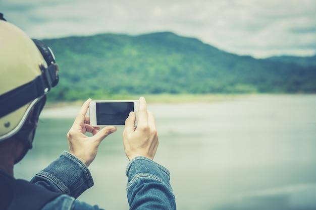 O smartphone móvel na mão toma a foto pelo turista ao céu e à nuvem