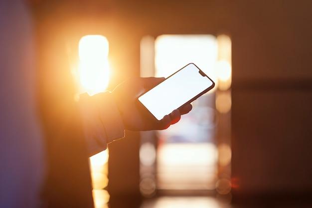 O smartphone na mão do cara contra o pôr do sol.
